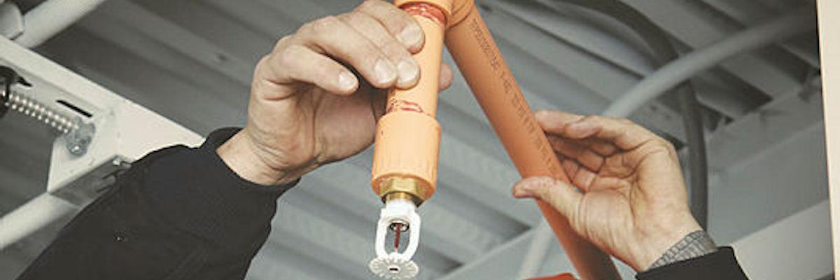 Funcionários instalam o sprinkler contra incêndio CPVC BlazeMaster® para atender um cronograma agressivo e um orçamento apertado